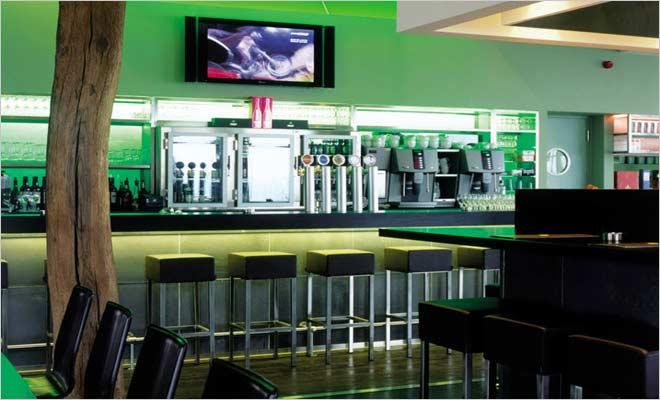 moderne bar met krukken en groene verlichting in hotel de pits in ...
