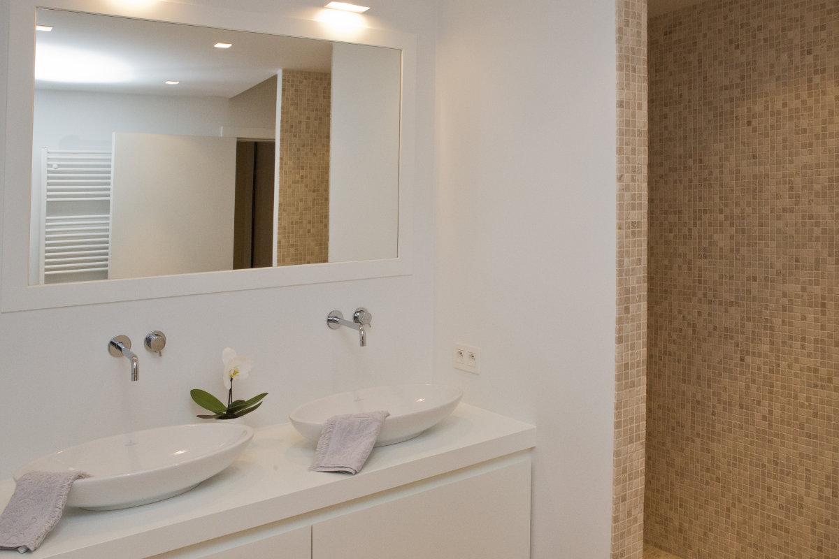 Appartement aan zee met wit interieur en houtaccenten binnenkijken - Witte badkamer en bruin ...